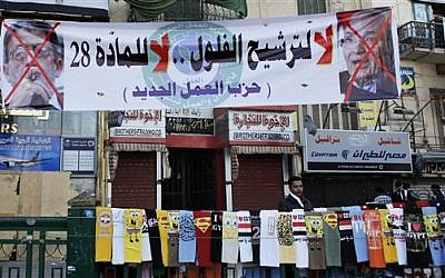 """An Egyptian street vendor with t-shirt display at a rally at Tahrir square in Cairo on Friday. The banner reads """"No for the former regime candidates, no for article 28, the New Labor Party,"""" and has pictures of two presidential hopefuls crossed out. (photo credit: AP Photo/Nasser Nasser)"""