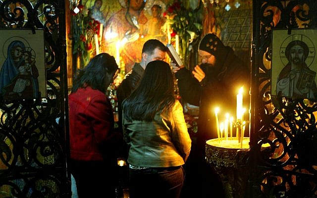 A Coptic priest blesses pilgrims in the Church of the Holy Sepulchre, Jerusalem (photo credit: Olivier Fitoussi/Flash90)