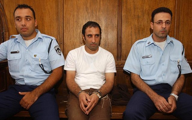 Hagai Amir, seen here flanked by policemen during a court appearance, will soon be released from prison (photo credit: Flash90)