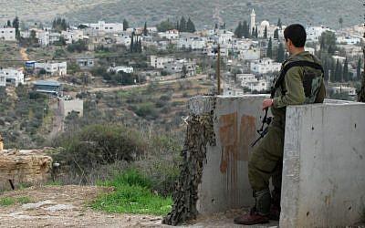 An IDF soldier stands guard overlooking the Palestinian village of Qadum. (photo credit: Gili Yaari/Flash90)