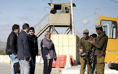 Illustrative photo of soldiers checking Palestinians at a roadblock outside the West Bank village of Yasuf, near Nablus. (Abir Sultan/Flash90)