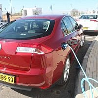 A Renault electric car recharges at a charging station in Ramat Hasharon (Photo credit: Roni Schutzer/Flash90)