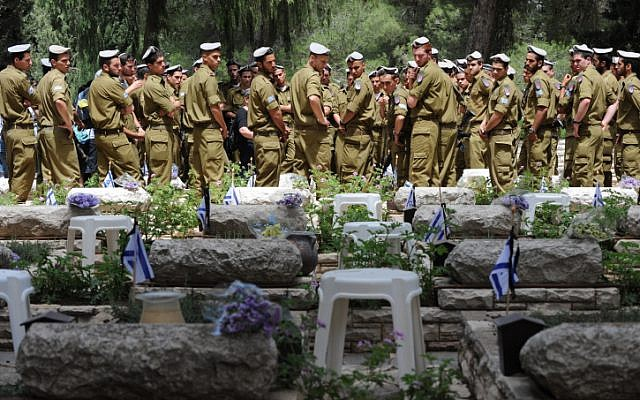 Illustrative photo of soldiers standing near the graves of fallen comrades at the Mount Herzl military cemetery, Jerusalem, ahead of Memorial Day, 2012. (photo credit: Gili Yaari/Flash90)