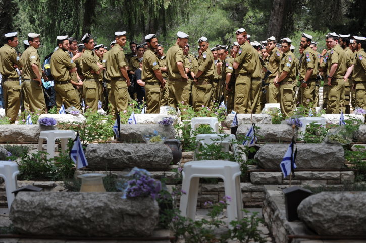 Israeli soldiers stand near the graves of fallen IDF soldiers in the Mt. Herzl military cemetery before the Memorial Day for fallen soldiers and victims of terrorism in 2010 (photo credit: Gili Yaari/Flash90)