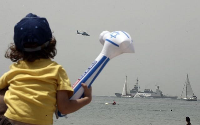 A child watches the naval flotilla during last year's Independence Day celebrations (photo credit: Abir Sultan/Flash90)