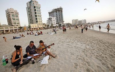 Young Israelis on a Tel Aviv beach (Illustrative photo credit: Miriam Alster/Flash90)