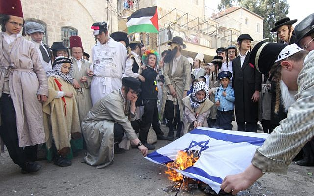 Neturei Karta activists wave a Palestinian flag as they burn the Israeli flag in the Meah Shearim neighborhood of Jerusalem on Purim last year. (photo credit: Nati Shohat/Flash90)