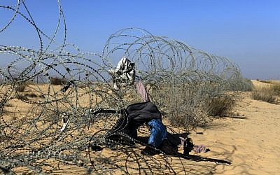The border fence between Israel and Egypt with clothing left during illegal crossings (photo credit: Tsafrir Abayov/Flash90)