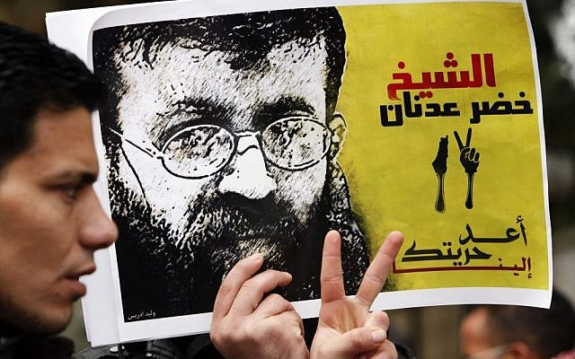 A Palestinian man holds up a poster of Palestinian prisoner Khader Adnan in protest of Adnan's previous administrative detention, February 10, 2012. (Sliman Khader/Flash90)