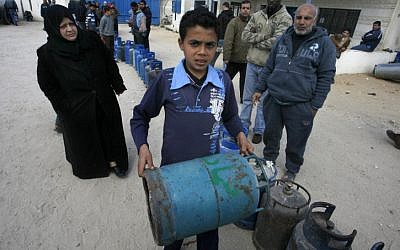 Palestinians wait to fill gas canisters at a fuel station in Khan Younis (photo credit: Abed Rahim Khatib/Flash 90)