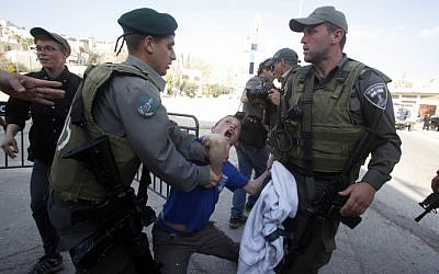 Border policemen scuffle with a boy outside the Beit Hamachpela building in Hebron on Wednesday. (photo credit: Uri Lenz/Flash 90)