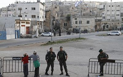 Settlers and border policeman outside Beit Hamechpela in Hebron on the day of the eviction (photo credit: Miriam Alster/Flash90)