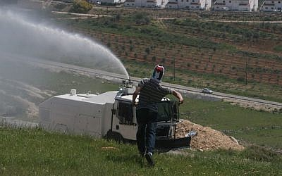 A protester and a water cannon at Nebi Salah in early April (photo credit: Issam Rimawi/Flash 90)