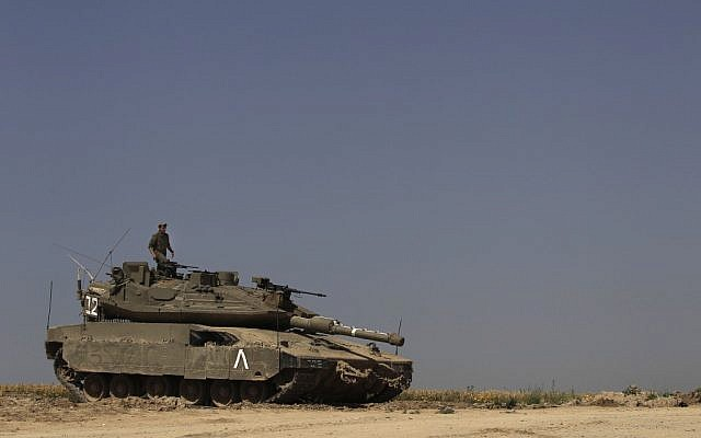 An IDF soldier stands on top of a tank  (Illustrative photo; credit: Tsafrir Abayov/Flash90)