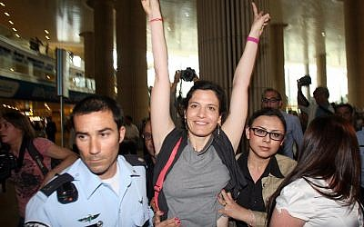 A pro-Palestinian activist is detained by police at the airport Sunday (photo credit: Gideon Markowicz/Flash90)