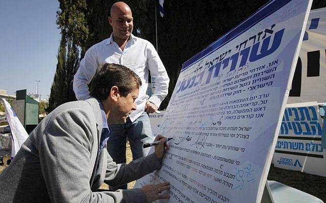 MK Yitzhak Herzog at the 'Suckers' Tent' signing the petition calling for universal service law to replace the Tal Law. April 23 2012. (photo credit: Miriam Alster/Flash90)