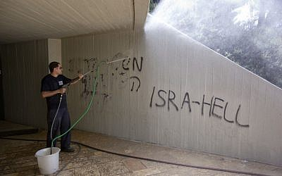 A worker cleans graffiti sprayed at Ammunition Hill on Monday (photo credit: Yossi Zamir/Flash 90)