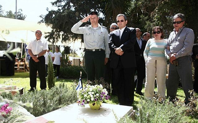 Ehud Barak stands at the graves of soldiers who were killed in the line of duty, at Kibbutz Mishmar Hasharon on Monday. (photo credit: Yehoshua Yosef/Flash90)