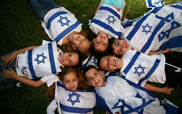 Children wave Israeli flags on last year's Independence Day. (photo credit: Yehoshua Yosef /Flash90)