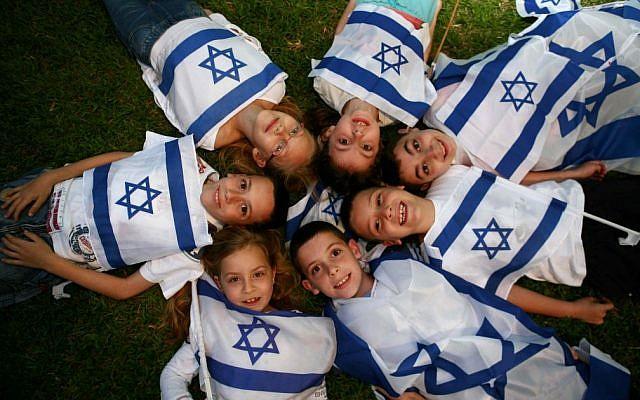 Illustrative: Children wave Israeli flags on last year's Independence Day. (photo credit: Yehoshua Yosef /Flash90)
