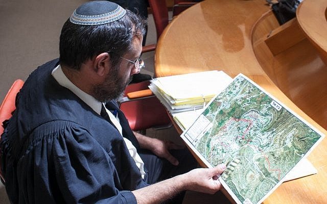 A lawyer looks over a map of Beit El prior to a High Court hearing in 2012 (Noam Moskowitz/Flash90)