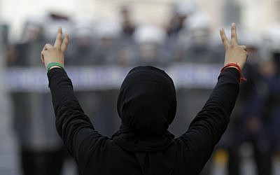 A Bahraini anti-government demonstrator gestures toward riot police during March protests in Manama (photo credit: AP/Hasan Jamali)