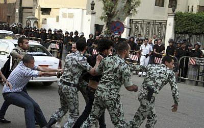 A protester is detained by security forces in front of the Saudi Embassy in Cairo, April 28, 2012 (photo credit: Ahmed Gomaa/AP)