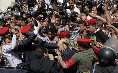 Former Egyptian Vice President Omar Suleiman, center, is escorted by military police as he prepares to submit his candidacy papers at the Higher Presidential Elections Commission on Sunday. (photo credit: AP/Amr Nabil)