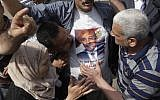 Supporters of Omar Suleiman kiss a T-shirt with his image (photo credit: AP/Amr Nabil)