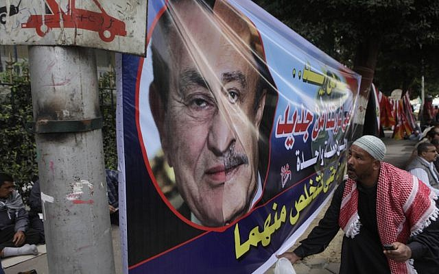 "An Egyptian holds a banner showing a half face portrait of ousted president Hosni Mubarak, left, and his former spy chief Omar Suleiman during a rally in Tahrir Square, Cairo, Friday. The Arabic text reads ""We will protect our revolution"". (photo credit: AP/Amr Nabil)"