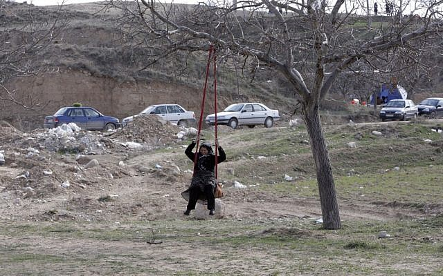 An Iranian woman plays on a swing during a picnic marking the ancient festival of Sizdeh Bedar. (photo credit: AP/Vahid Salemi)