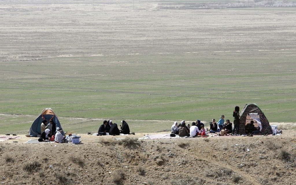 Iranian families celebrating the ancient festival of Sizdeh Bedar outdoors. (photo credit: AP/Vahid Salemi)
