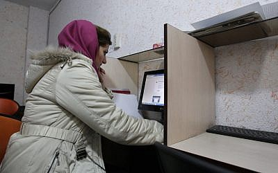 Illustrative photo of a Muslim woman wearing a head cover at an internet cafe in central Tehran. (photo credit: Vahid Salemi/AP)