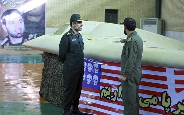 Chief of the aerospace division of Iran's Revolutionary Guards, Amir Ali Hajizadeh (left), near the captured US RQ-170 Sentinel drone in April 2012. (photo credit: AP/Sepahnews)