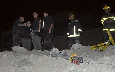 Police stand next to a rocket that landed in Eilat in early April (photo credit: AP/Yehuda Ben Itah)