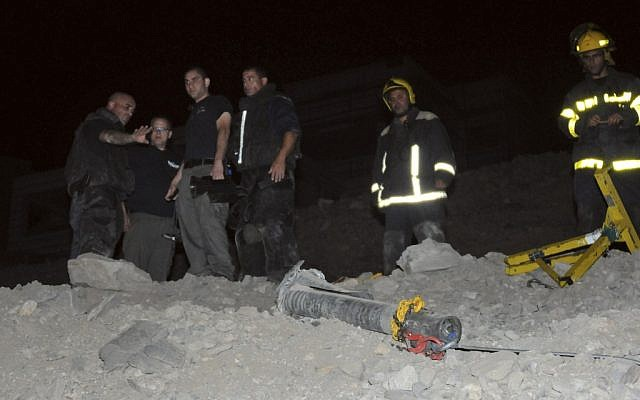 Police stand next to a rocket that landed in Eilat in early April 2012 (photo credit: AP/Yehuda Ben Itah)
