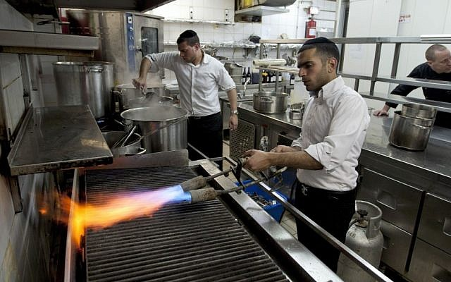 Chef Noam Dekkers , in the back, watches workers of the Tel Aviv-Jaffa rabbinate blow-torch the grill stove in one of the kitchens in Liliyot restaurant making it kosher for the Jewish holiday of Passover. (photo credit: AP)