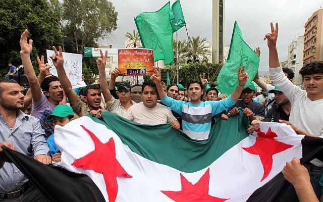 Supporters of an Islamic group and of former Lebanese prime minister Saad Hariri's Future Movement wave party flags and a giant Syrian revolution flag during a demonstration against the Syrian regime to show solidarity with the Syrian people after Friday prayers in Beirut, Lebanon (photo credit: Bilal Hussein/AP)