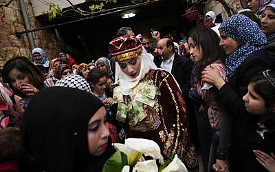 Maha Surougi (center) walks towards Thaer Qasem, the groom, during their wedding in the West Bank village of Deir Istiya, near Nablus. The bride and the groom, Syrian citizens with Palestinian roots, were invited by the Palestinian government to celebrate their marriage in the West Bank. (photo credit: AP/Bernat Armangue)