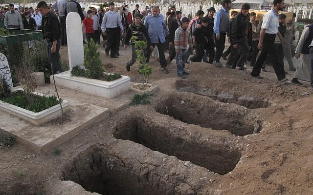 Mourners walk past open graves at a cemetery during a funeral for four people killed in a raid by government forces in a neighborhood of Damascus, Syria, April 7, 2012 (photo credit: AP)