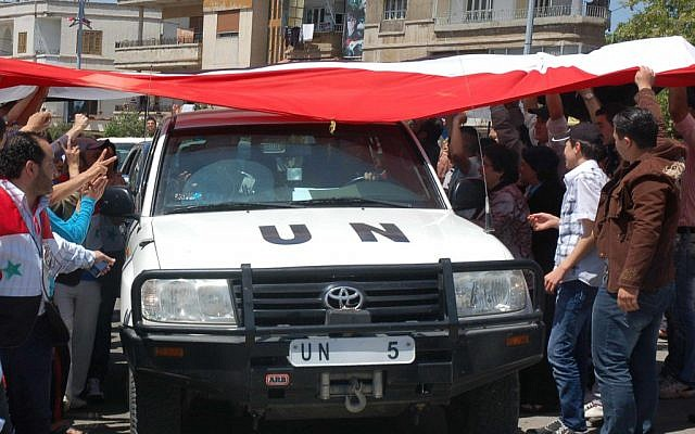 A UN vehicle drives through a crowd of Assad supporters in Homs (photo credit: AP/SANA)