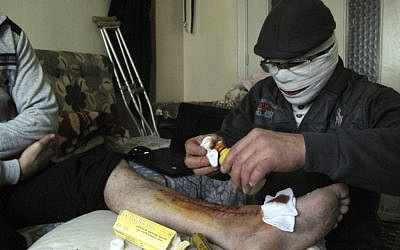 An injured man gets treated in a Damascus neighborhood Tuesday (photo credit: AP)