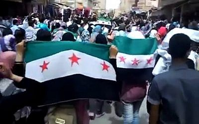 This image made from amateur video shows Syrians holding Syrian revolutionary flags during a demonstration in Deir el-Zour, Syria in April 2013.  (photo credit: AP /Ugarit News)