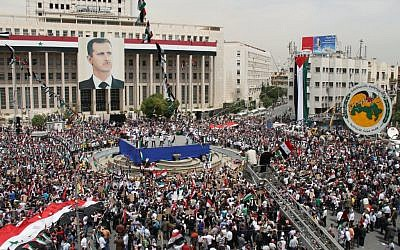 Pro-Syrian government demonstrators rally in Damascus, on Saturday (photo credit: AP / Bassem Tellawi)