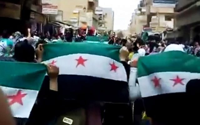 Syrians hold Syrian revolutionary flags during a demonstration in Deir el-Zour on Thursday. (photo credit: AP/Ugarit News)