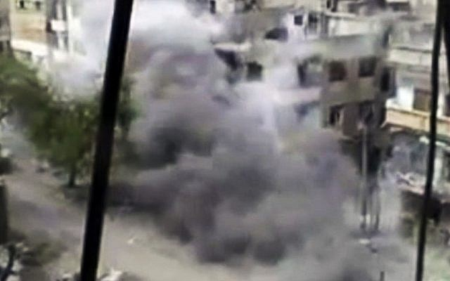 Image from amateur video purportedly showing shelling in Homs hours before the first UN observers arrive in Damascus (photo credit: AP/Shaam News Network)