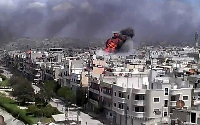 This image, taken from an amateur video Friday, purports to show an explosion amid heavy shelling in the Khaldiyeh area of Homs, Syria. (photo credit: Shaam News Network via AP video; AP cannot independently verify the location or authenticity of this material)