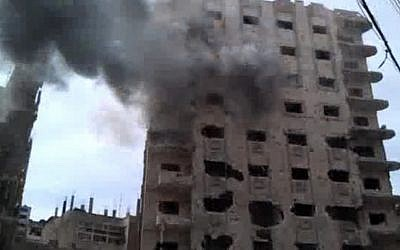 A building damaged by government shelling Saturday in Homs, Syria. (photo credit: AP/Bambuser)
