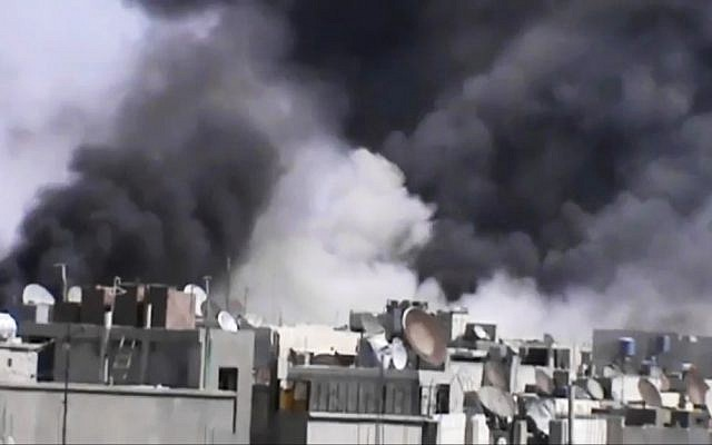 Smoke rises from buildings following purported shelling in Homs, Syria, in video distributed Wednesday. (photo credit: AP/Shaam News Network via AP video)