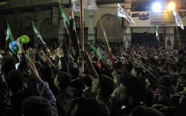 Syrians raise their hands vowing to continue fighting until President Bashar Assad's regime falls during a Damascus protest last week. (photo credit: AP)